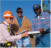 Close up of three men reviewing paperwork at a job site.